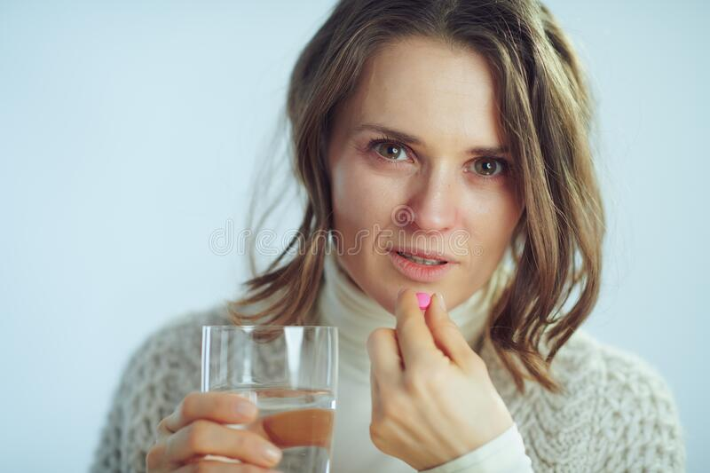 Sick elegant housewife with cup of water eating pill royalty free stock photos