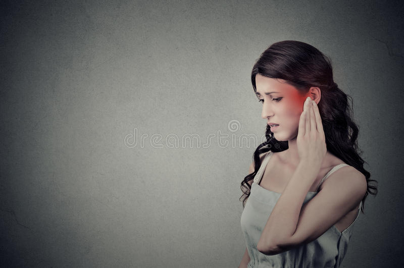 Sick female having ear pain touching her painful head temple colored in red stock photo