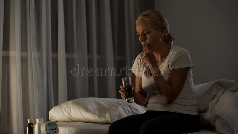 Sick female suffering from depression taking antidepressants, self-treatment royalty free stock images