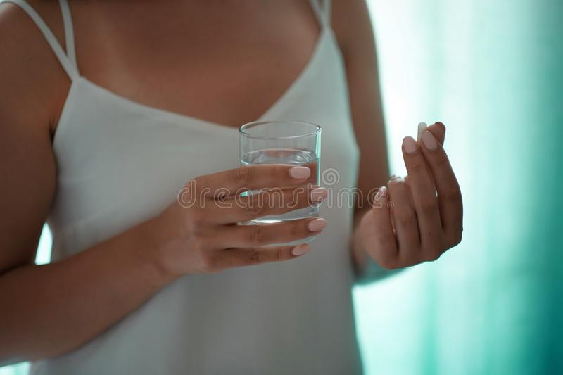 Sick female taking medicines, antidepressant, painkiller or antibiotic. Young lady drinking contraceptives. Pharmacy and stock image