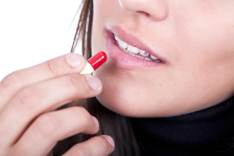 Sick female taking a pill royalty free stock images