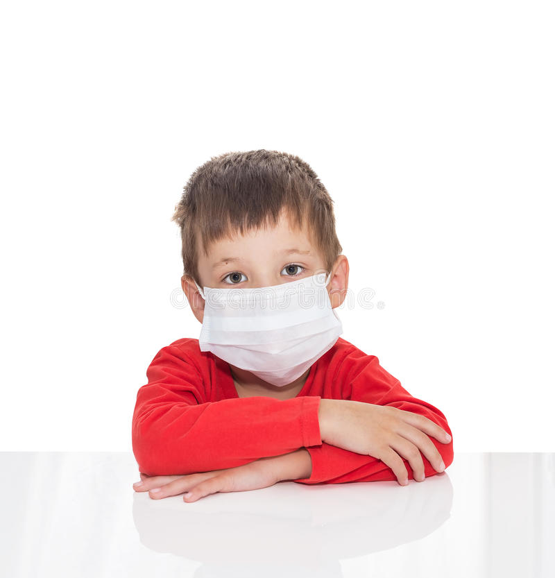 The sick five-year-old boy sits at a white table with medicine healthcare mask for is protection again virus. Isolated on a white background stock photo