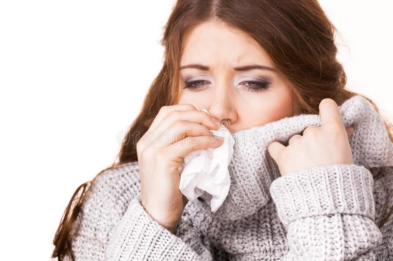 Sick freezing woman sneezing in tissue royalty free stock photography