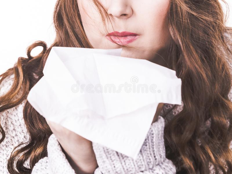Sick freezing woman sneezing in tissue royalty free stock photo