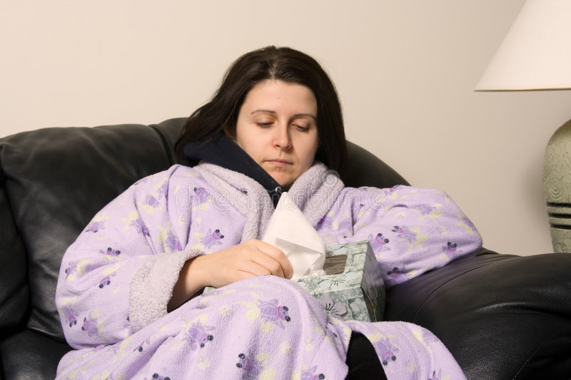 Sick girl. Woman with a cold reaching out for a tissue royalty free stock image