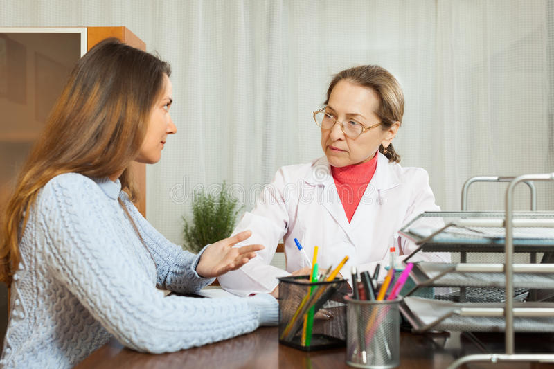 Sick girl complaining to doctor. About symptoms of malaise royalty free stock photo