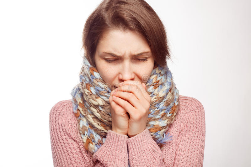 Sick girl coughing on white background. Young woman in scarf coughing and covering mouth with hands on white background stock image