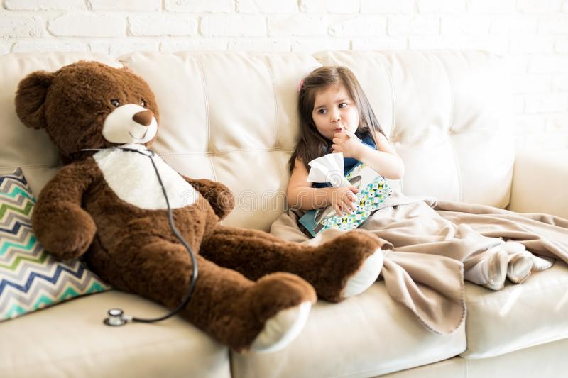 Sick girl with doctor teddy bear on sofa stock images