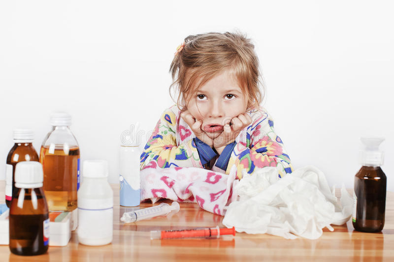 Sick girl hoping for the new miracle drug. A little sick girl with many medicine bottles royalty free stock photos