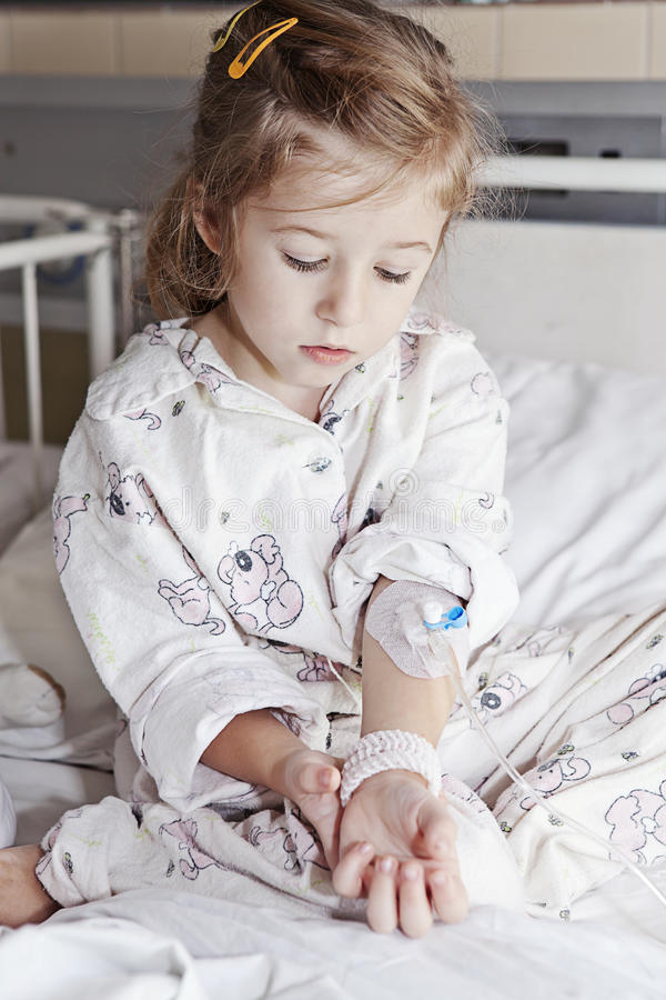 Sick girl in hospital. Little sick girl with a cannula in her arm royalty free stock photo
