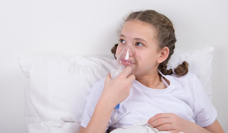 sick girl lying in bed holding mask for inhalation stock photography