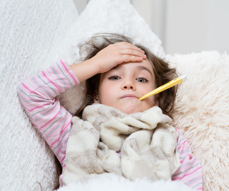 Sick girl lying in bed with a thermometer in mouth and touch his forehead royalty free stock image