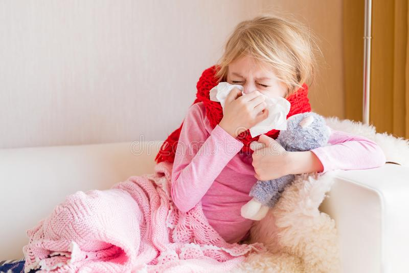 Sick girl with runny nose sitting in sofa. At home stock images