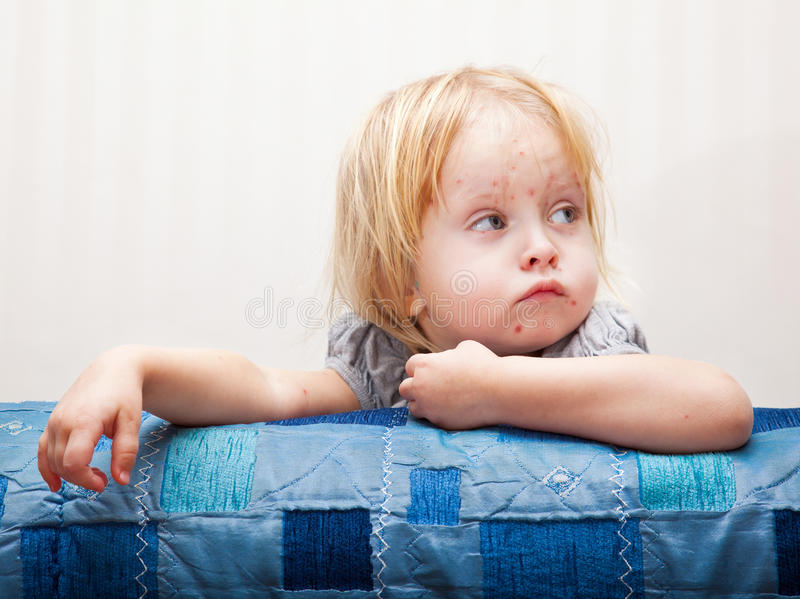 A sick girl is sitting near the bed stock photos