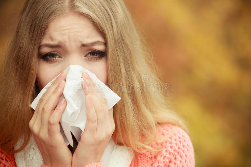 Sick ill woman in autumn park sneezing in tissue. royalty free stock photos