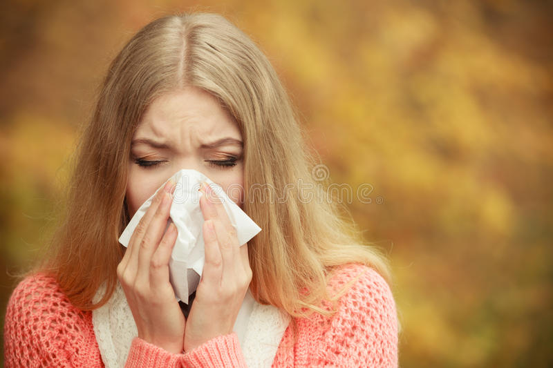 Sick ill woman in autumn park sneezing in tissue. stock images