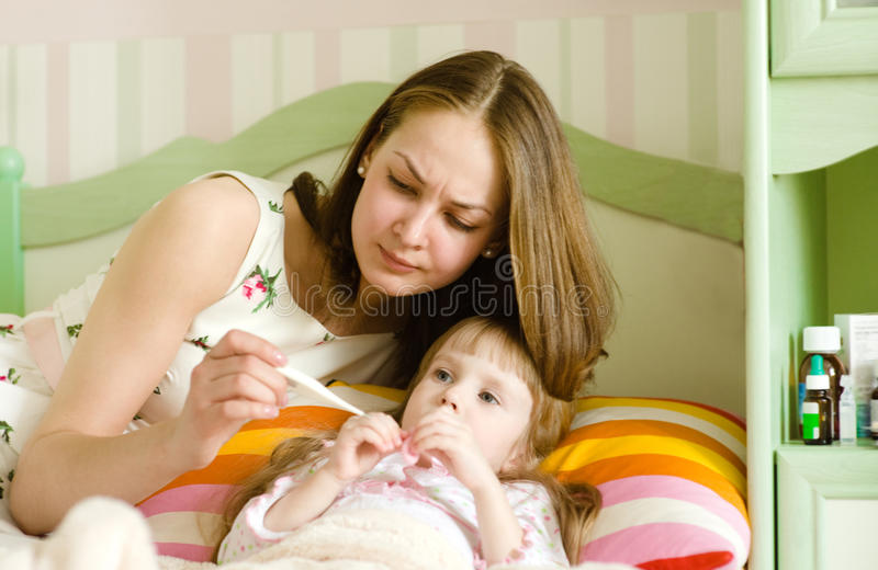 Sick kid with high fever laying in bed stock photos