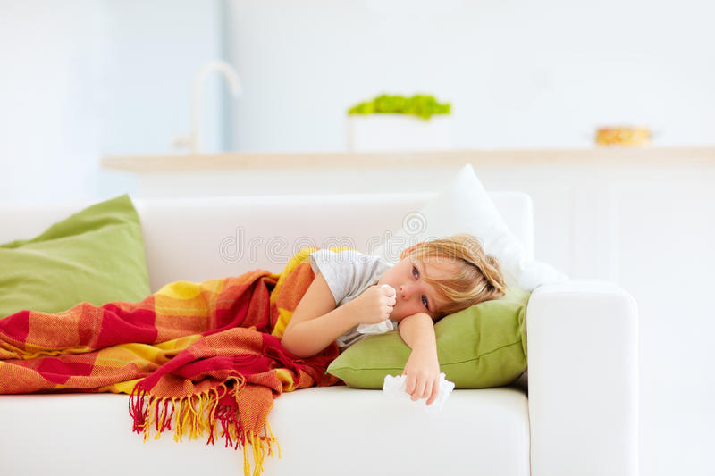 Sick kid with runny nose and fever heat lying on couch at home. Sick boy, kid with runny nose and fever heat lying on couch at home stock photos