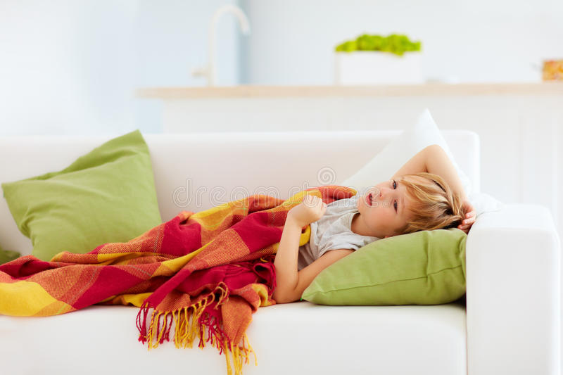 Sick kid with runny nose and fever heat lying on couch at home. Sick boy, kid with runny nose and fever heat lying on couch at home royalty free stock photography