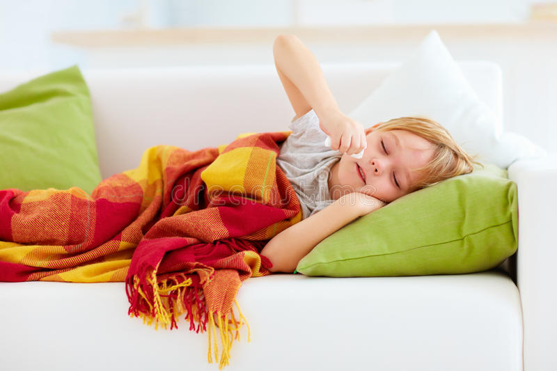 Sick kid with runny nose and fever heat lying on couch at home. Sick boy, kid with runny nose and fever heat lying on couch at home stock images