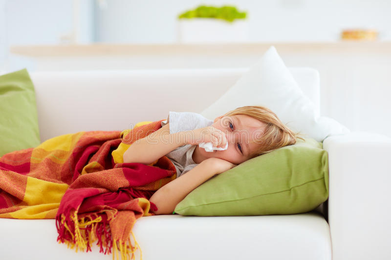 Sick kid with runny nose and fever heat lying on couch at home. Sick boy, kid with runny nose and fever heat lying on couch at home stock photo