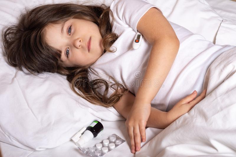 Sick kid with thermometer laying in bed and taking temperature. Checking temperature using thermometer. royalty free stock image