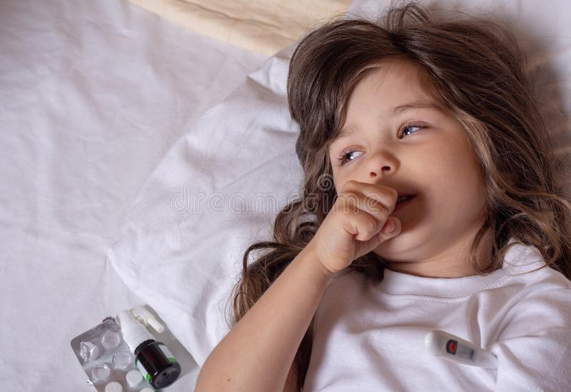 Sick kid with thermometer laying in bed and taking temperature. Checking temperature using thermometer. royalty free stock photo