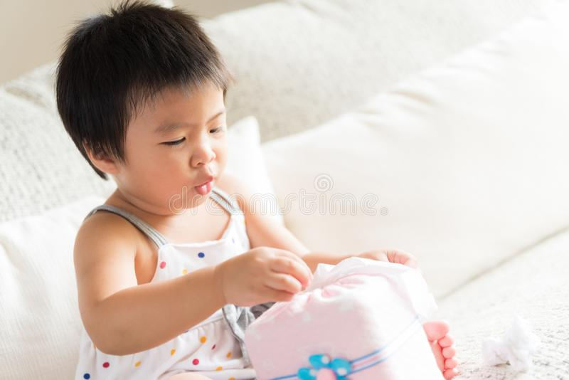 Sick little Asian girl wiping or cleaning nose with tissu royalty free stock image