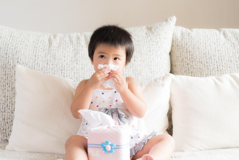 Sick little Asian girl wiping or cleaning nose with tissue sitting on sofa at home. Medicine and health care concept. stock image