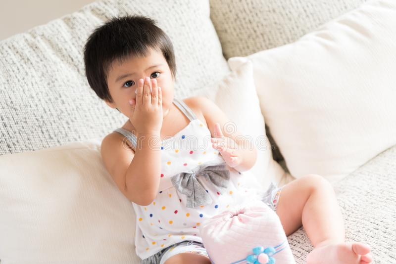 Sick little Asian girl wiping or cleaning nose with tissue stock photo