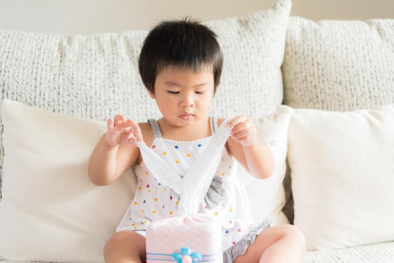 Sick little Asian girl wiping or cleaning nose with tissue sitting on sofa at home. Medicine and health care concept. royalty free stock photo