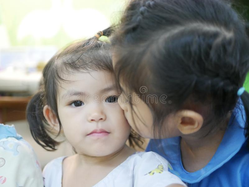 Sick little baby girl, in a hospital`s pediatric patient room, got an encouraging kiss from her older sister who came visiting stock photo