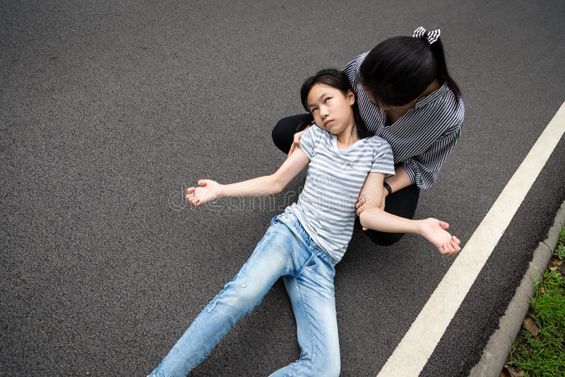 Sick little child girl with epileptic seizures on the street,daughter suffering from seizures,illness with epilepsy during seizure. Attack,asian young women or royalty free stock photography