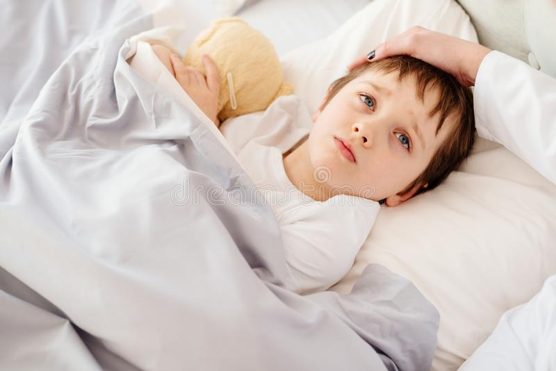 Sick little child with temperature in bed. Hand of doctor on his forehead royalty free stock image