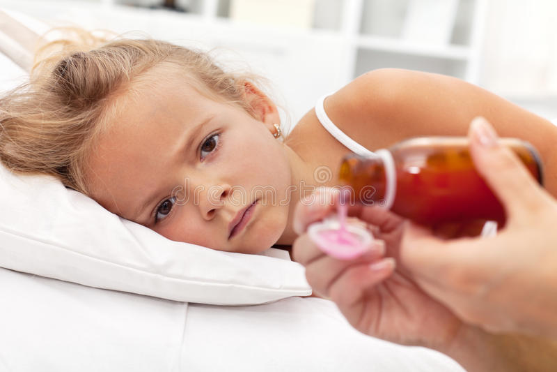 Sick little girl awaiting medication stock photo