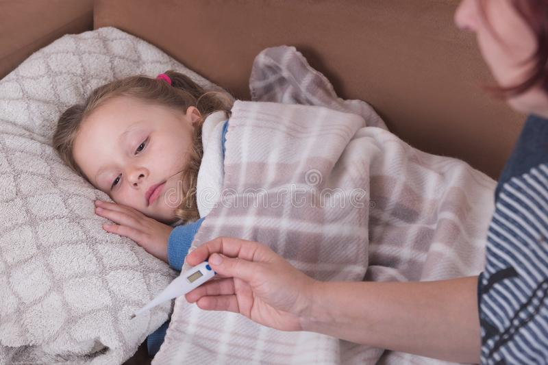 Sick little girl in bed. Mother with thermometer is sitting near the bed royalty free stock images