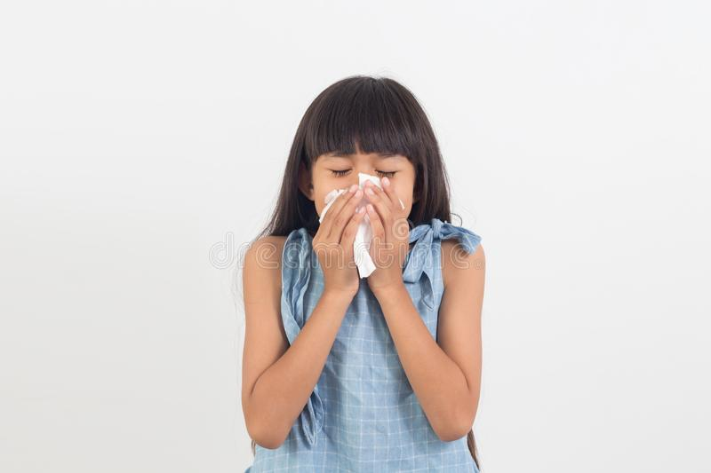 Sick little girl blowing her nose isolated on white stock photography