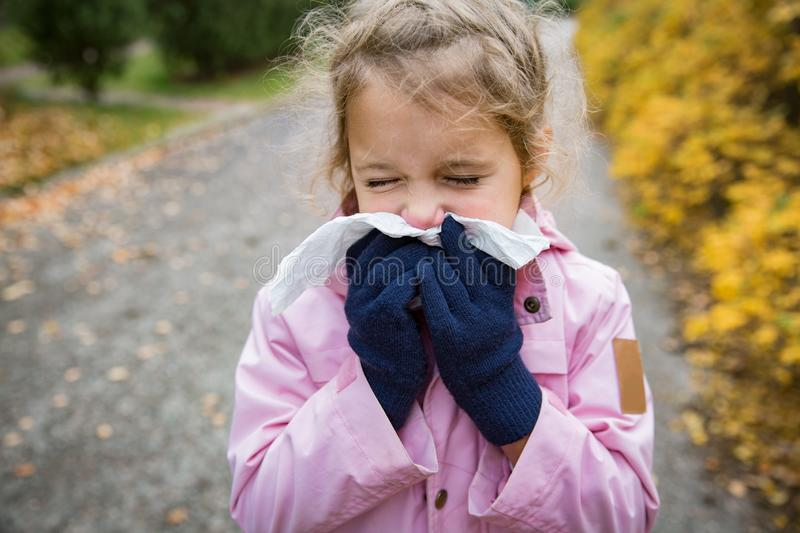 Sick little girl with cold and flu standing outdoors. royalty free stock image
