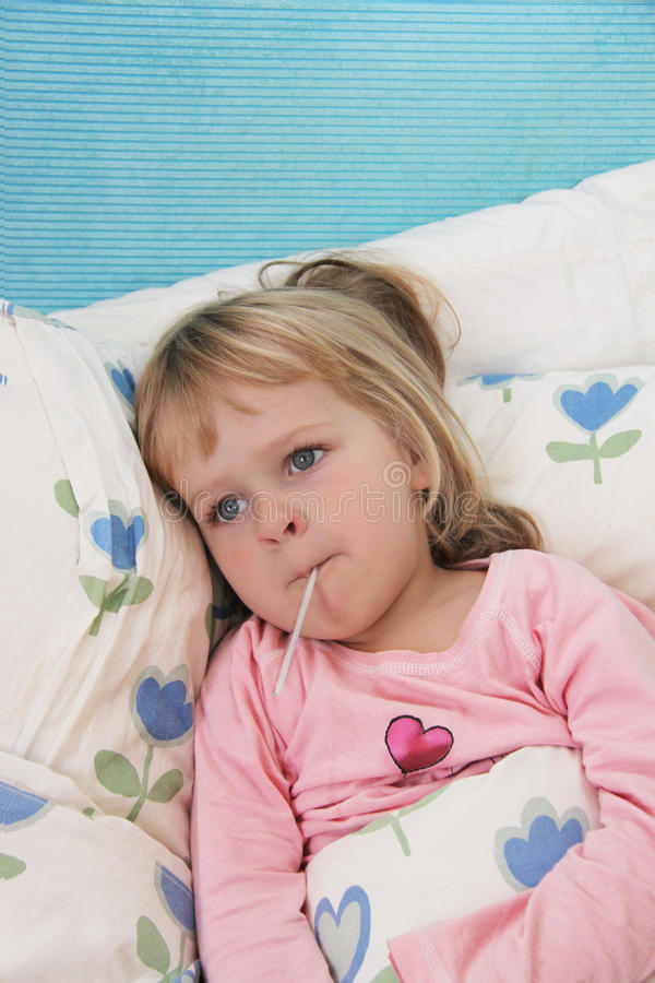 Sick little girl with fever thermometer