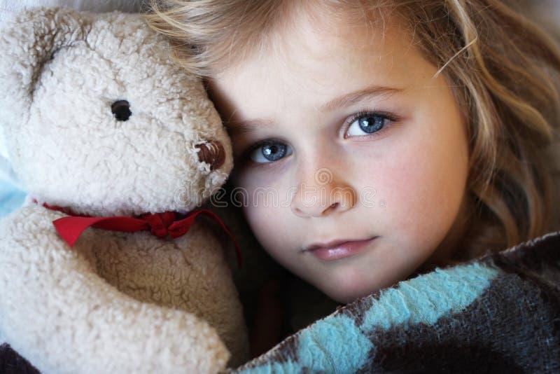 Sick little girl with teddybear stock photography
