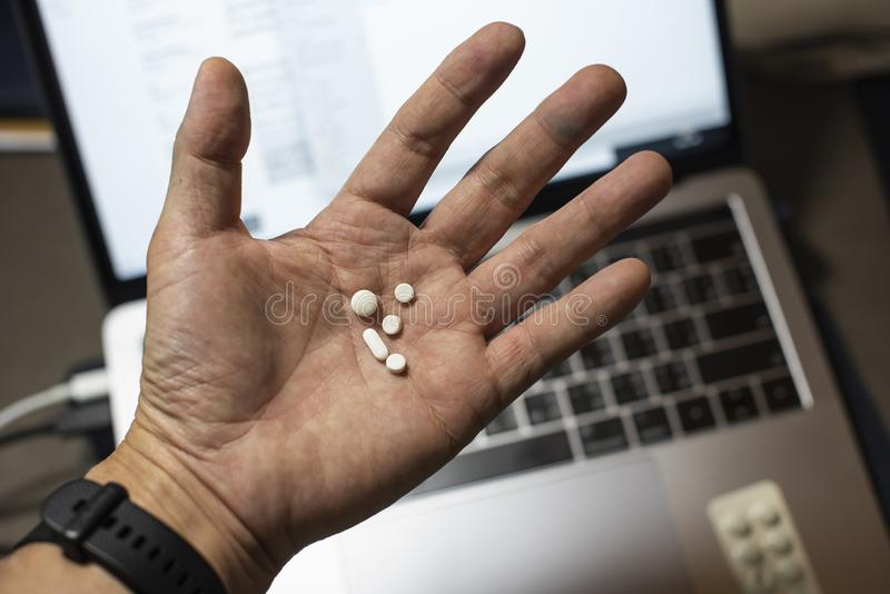 Sick male home office worker taking pills in front of his working space, during his working deadline night. royalty free stock images