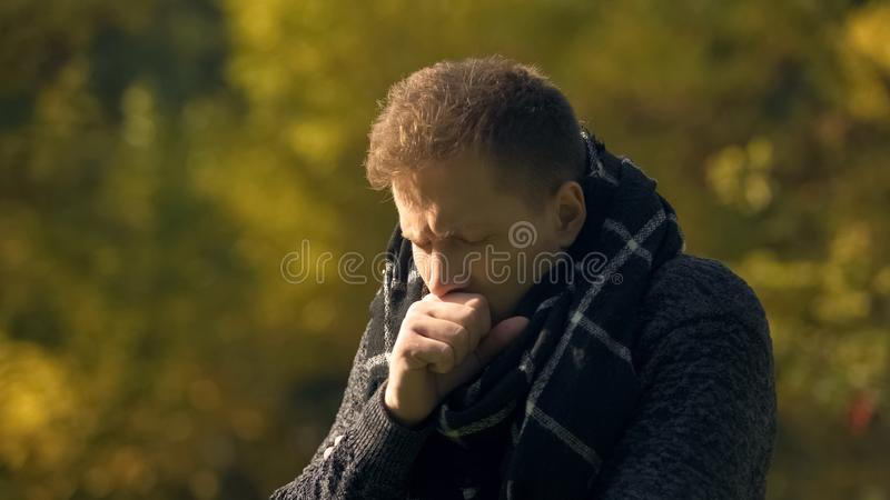 Sick male in scarf coughing in park, caught cold, pneumonia risk, infection stock image
