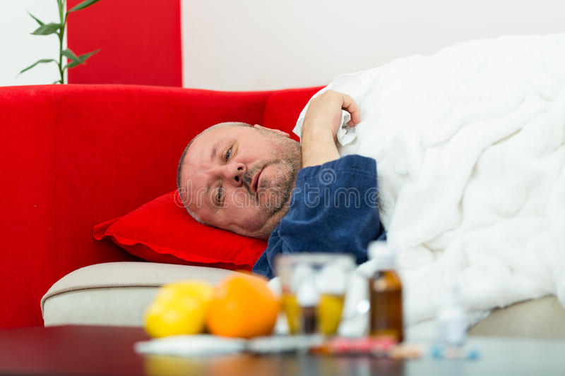 Sick man in bed with drugs and fruit on table.  stock photos