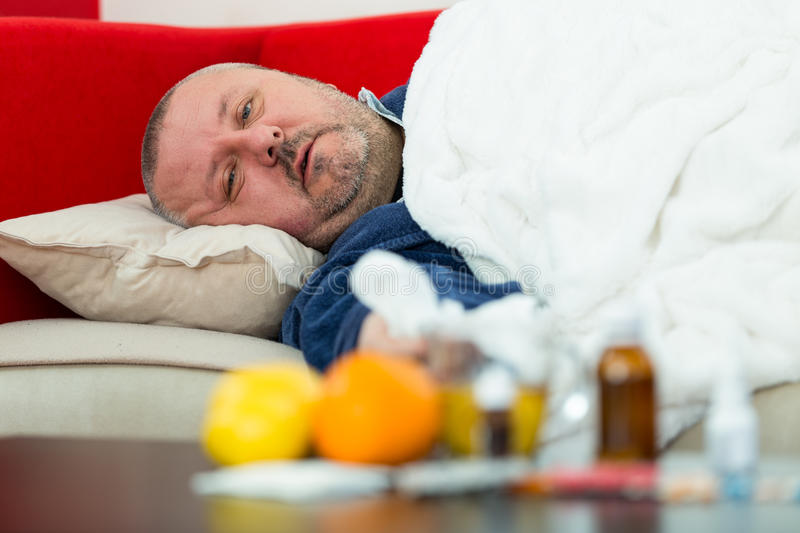 Sick man in bed with drugs and fruit on table.  royalty free stock photos