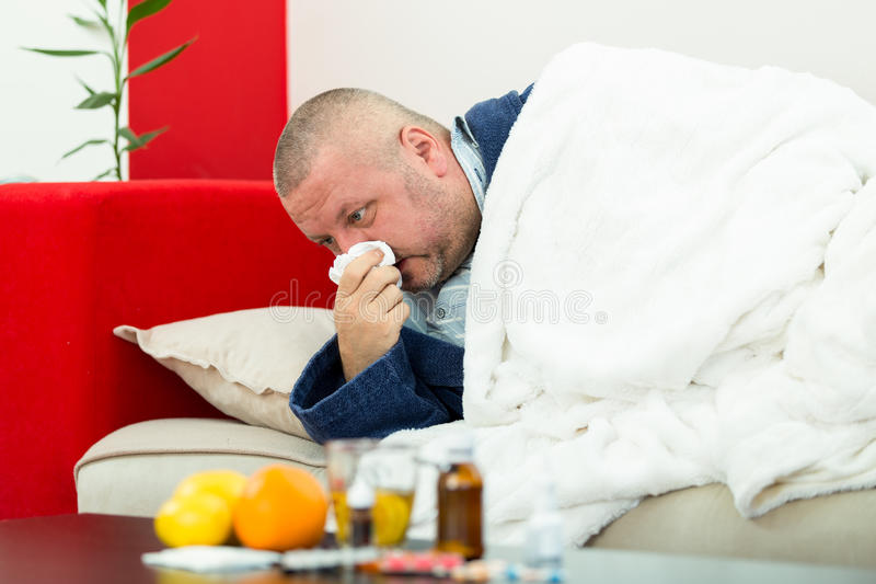Sick man in bed with drugs and fruit on table.  stock photo