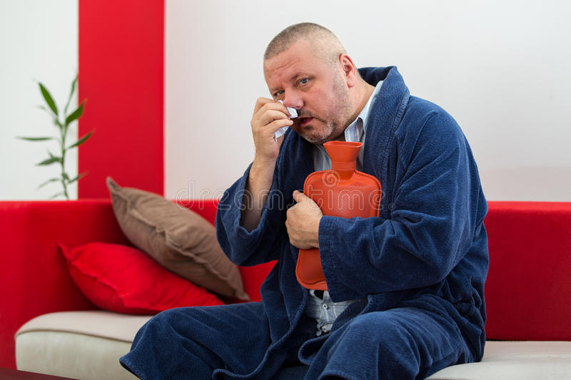 Sick man in bed having a headache holding a hot-water bottle.  stock photo