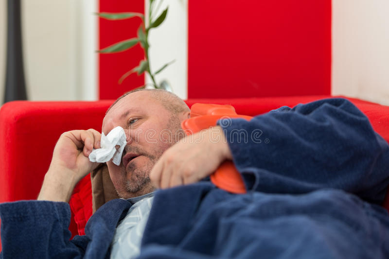 Sick man in bed having a headache holding a hot-water bottle.  royalty free stock photography