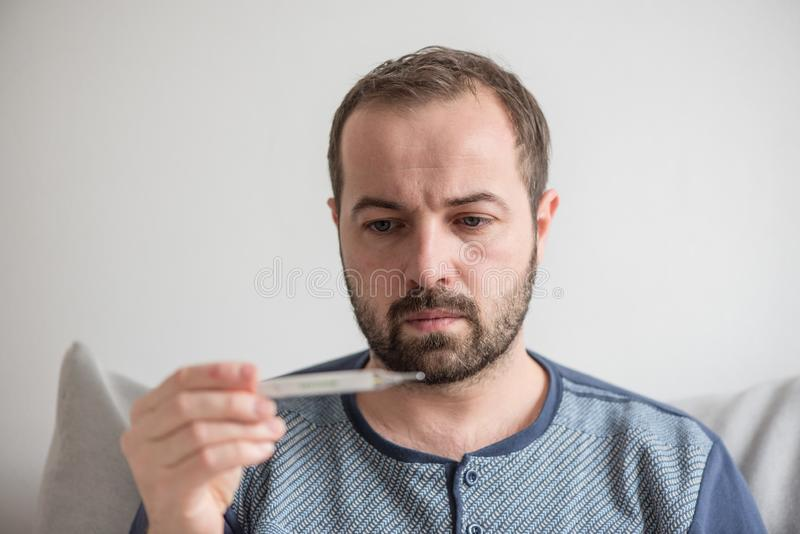 Sick man checks the body temperature with a mercury thermometer. Theme of viral diseases, flu, colds.  royalty free stock image