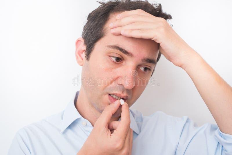 Head of sick man eating medicine pill. Sick man eating aspirin pill medication royalty free stock photography