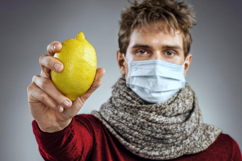 Sick man holding lemon. Photo of man wears protective mask against infectious diseases and flu. Healthcare concept stock photos